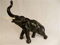 Large bronze black elephant with ivory tusks